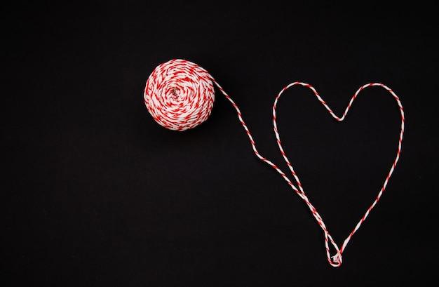 Auf einem schwarzen hintergrund ist eine schnurkugel rot und weiß. fäden in form eines herzens ausgelegt. das konzept des valentinstags.