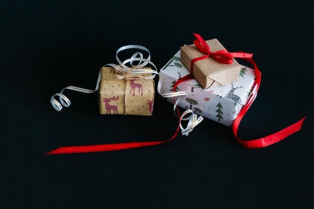 Auf einem schwarzen hintergrund stehen weihnachtsgeschenke, die in geschenkpapier eingewickelt und mit bändern zusammengebunden sind, eine kleine bastelschachtel mit einem roten band, eine große schachtel mit einem weißen band mit gold