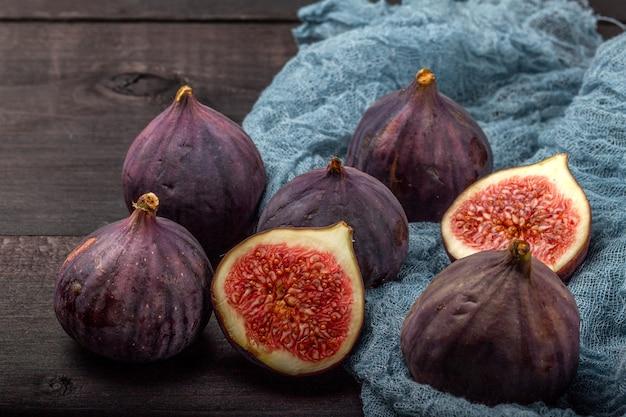 Auf einem schwarzen holztisch liegen die früchte frischer feigen. schöne blaue feigenfrüchte schließen