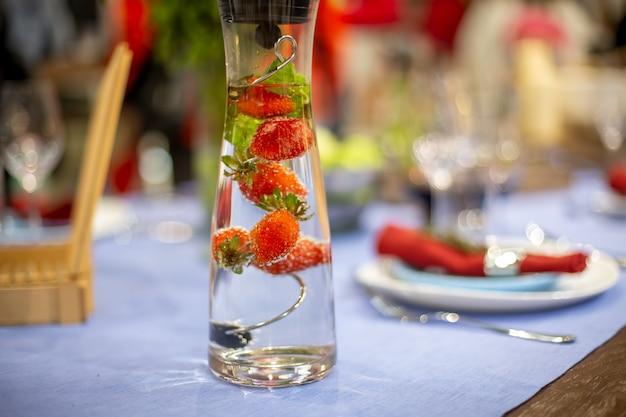 Auf einem servierten blauen tisch steht eine mit wasser und erdbeeren gefüllte karaffe. nahaufnahme, weichzeichner. servierter tisch ist im hintergrund in unschärfe