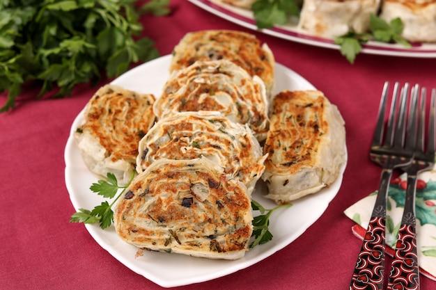 Auf einem teller liegen gebratene lavaschröllchen mit kartoffeln und champignons