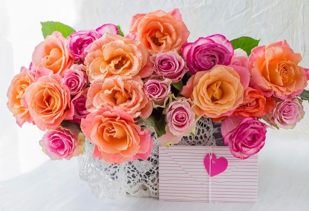 Auf einem tisch einen blumenstrauß mit orangen rosen in einem weißen korb und einen umschlag mit herz für