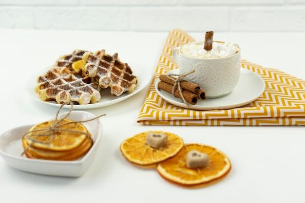 Auf einem tisch liegt der frühe frühstückskaffee mit marshmallows und einer zimtstange sowie belgischen waffeln