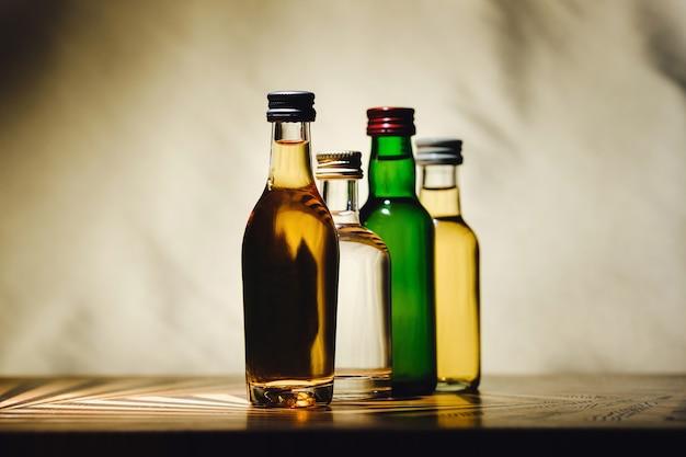Auf einem tisch stehen verschiedene alkoholflaschen an einem licht