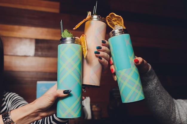 Auf einem tisch steht ein erfrischendes getränk mit einer thermoskanne aus obst und minze.