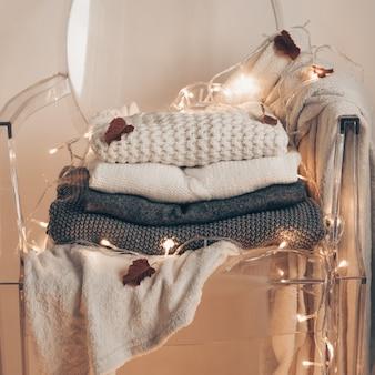 Auf einem transparenten plastikstuhl - warme pullover. stapel gestrickter kleidung, pullover, strickwaren, herbst-winter-konzept.