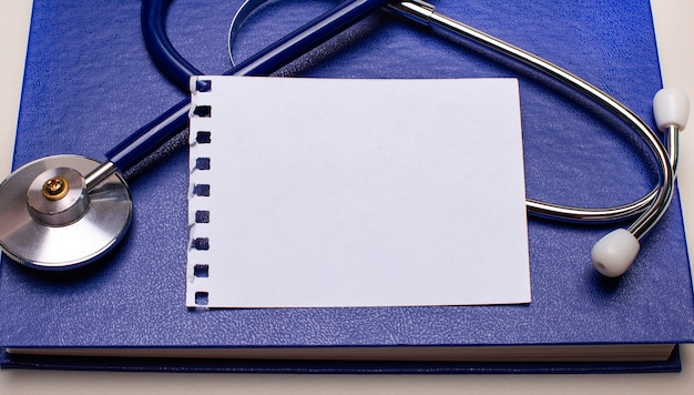Auf einem weißen desktop, einem blauen notizblock, einem stethoskop und einem weißen blatt papier mit kopienraum. medizinisches konzept