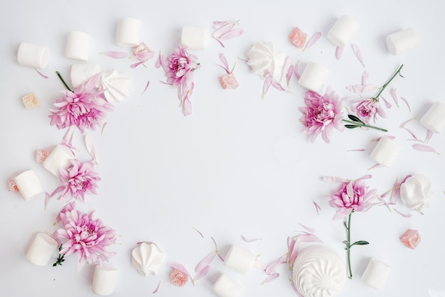 Auf einem weißen flanrahmen mit blumen, marshmallows und marshmallows draufsicht