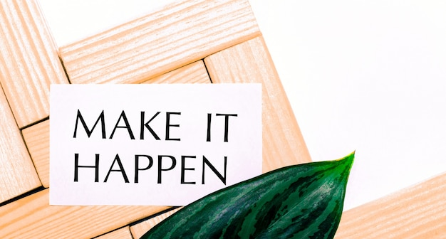 Auf einem weißen hintergrund holzbausteine, eine weiße karte mit dem text make it happen und ein grünes blatt der pflanze