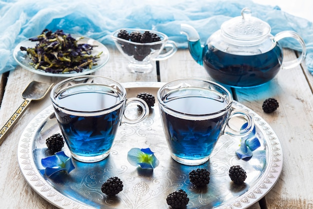 Auf einem weißen holztisch blauen tee in transparenten tassen, eine brombeere