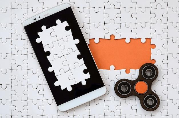 Auf einem weißen puzzle liegt ein modernes großes smartphone mit touchscreen und spinner