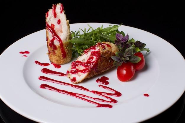 Auf einem weißen teller fleisch in semmelbröseln aus sesam, rucola, tomate, basilikum und ketchup. leckeres und schönes essen. kirschtomaten.