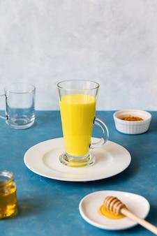 Auf einem weißen teller steht hohes glas mit goldener milch aus einem kräuter-kurkuma-getränk.
