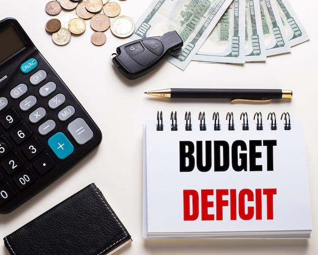 Auf einem weißen tisch stehen ein taschenrechner, ein autoschlüssel, bargeld, ein stift und ein notizbuch mit der aufschrift budget deficit