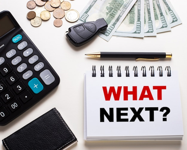 Auf einem weißen tisch stehen ein taschenrechner, ein autoschlüssel, bargeld, ein stift und ein notizbuch mit der aufschrift frage was nächstes