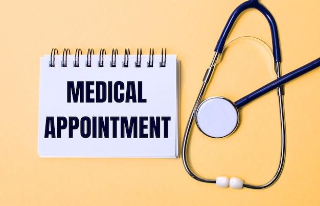 Auf einer beigen oberfläche ein stethoskop und ein weißer notizblock mit der aufschrift medical appointment. medizinisches konzept