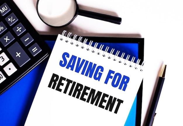 Auf einer blauen fläche in der nähe des taschenrechners, der lupe und des stiftes ein notizbuch mit der aufschrift saving for retirement