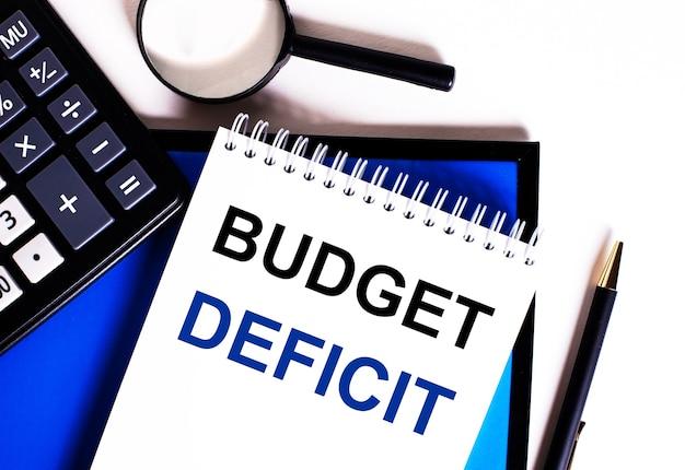 Auf einer blauen fläche neben dem taschenrechner, der lupe und dem stift ein notizbuch mit der aufschrift budget deficit