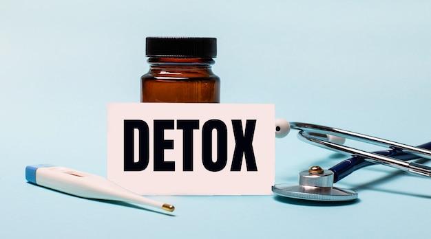 Auf einer blauen oberfläche - eine pillenflasche, ein stethoskop, ein elektronisches thermometer und eine karte mit der aufschrift detox. medizinisches konzept