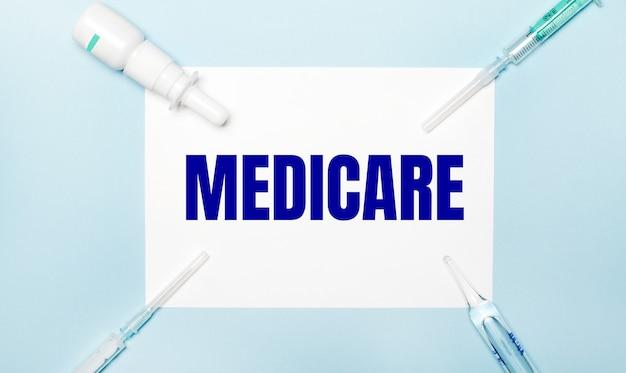 Auf einer blauen oberfläche spritzen, ein fläschchen mit medikamenten, eine ampulle und ein weißes blatt papier mit dem text medicare
