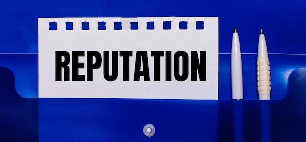Auf einer blauen oberfläche weiße stifte und ein blatt papier mit dem text reputation