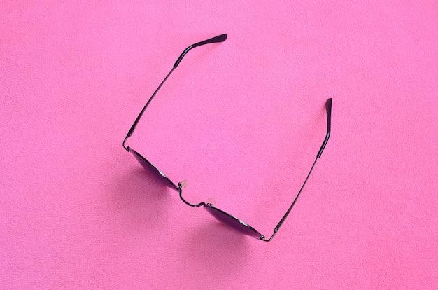 Auf einer decke liegt eine stilvolle schwarze sonnenbrille mit runder brille