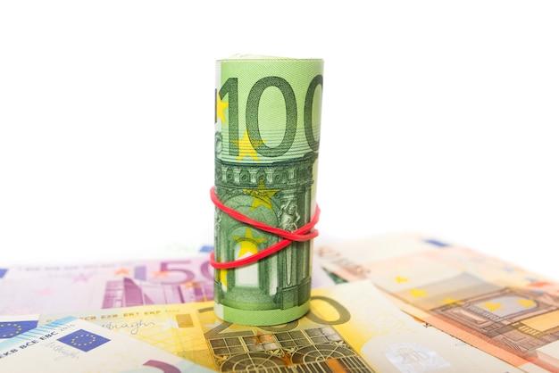 Auf einer geldoberfläche zu einer rolle von 100 euro verdreht. nahansicht.