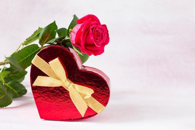 Auf einer geschenkbox in form eines herzens liegt eine rote rose
