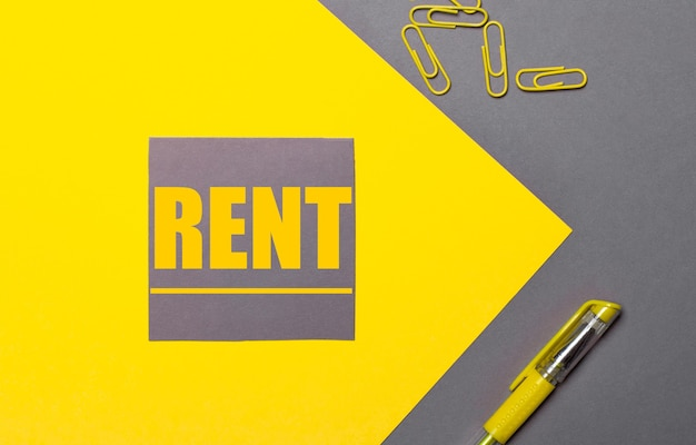 Auf einer grauen und gelben oberfläche ein grauer aufkleber mit gelbem text rent, gelbe büroklammern und ein gelber stift