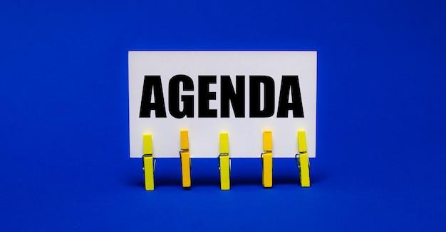 Auf einer hellblauen oberfläche auf gelben wäscheklammern eine weiße karte mit dem text agenda.