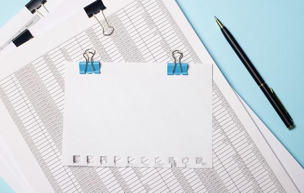 Auf einer hellblauen oberfläche befinden sich dokumente, ein stift und ein leeres blatt papier auf blauen büroklammern mit einem platz zum einfügen von text