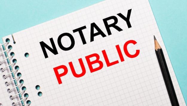 Auf einer hellblauen oberfläche ein kariertes notizbuch mit den worten notary public und einem schwarzen stift.