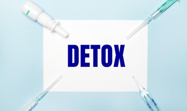 Auf einer hellblauen oberfläche spritzen, eine medizinflasche, eine ampulle und ein weißes blatt papier mit dem text detox. medizinisches konzept