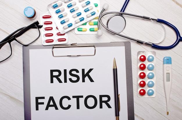 Auf einer hellen holzwand befindet sich papier mit der aufschrift risikofaktor, ein stethoskop, bunte pillen, gläser und ein stift. medizinisches konzept