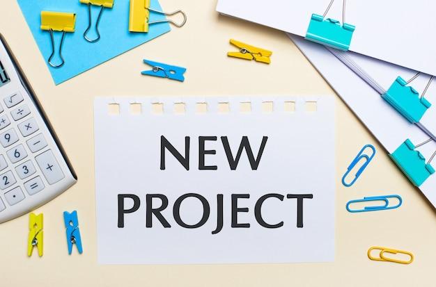Auf einer hellen oberfläche befinden sich stapel von dokumenten, ein weißer taschenrechner, gelbe und blaue büroklammern und wäscheklammern sowie ein notizbuch mit dem text neues projekt