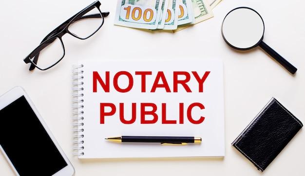 Auf einer hellen oberfläche dollars, gläser, eine lupe, ein telefon, ein stift und ein notizbuch mit der aufschrift notary public. geschäftskonzept