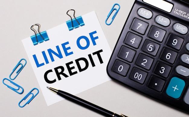 Auf einer hellen oberfläche ein taschenrechner, ein stift, blaue büroklammern und ein blatt papier mit dem text line of credit