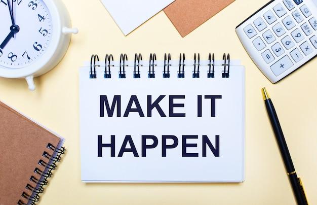 Auf einer hellen oberfläche ein weißer wecker, ein taschenrechner, ein stift und ein notizbuch mit dem text make it happen. flach liegen