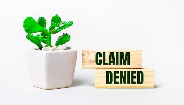 Auf einer hellen oberfläche eine pflanze in einem topf und zwei holzklötze mit dem text claim denied