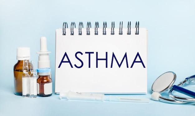 Auf einer hellen oberfläche eine spritze, ein stethoskop, fläschchen mit medikamenten, eine ampulle und ein weißer notizblock mit dem text asthma. medizinisches konzept.