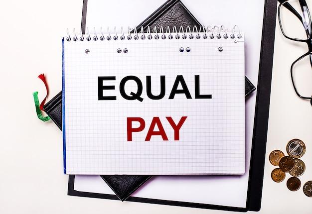 Auf einer hellen oberfläche gläser, münzen und ein notizbuch mit der aufschrift equal pay. geschäftskonzept.