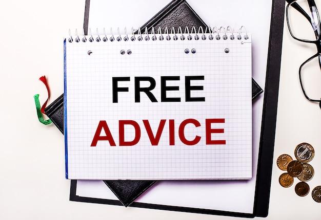 Auf einer hellen oberfläche gläser, münzen und ein notizbuch mit der aufschrift free advice