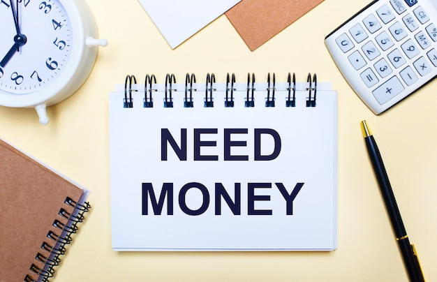 Auf einer hellen oberfläche stehen ein weißer wecker, ein taschenrechner, ein stift und ein notizbuch mit dem text geld benötigen