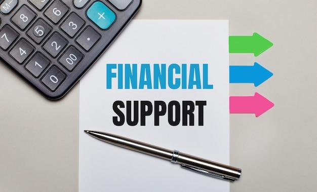 Auf einer hellgrauen oberfläche ein taschenrechner, ein weißes blatt mit dem text financial support, ein stift und helle mehrfarbige aufkleber