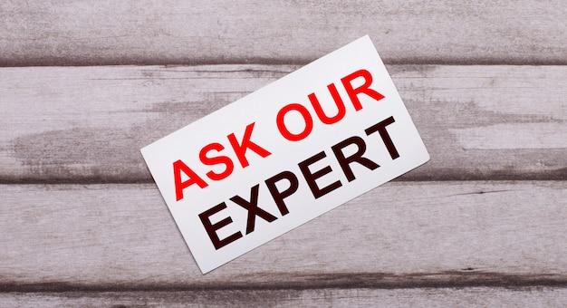 Auf einer holzoberfläche befindet sich eine weiße karte mit rotem text. fragen sie unseren experten.