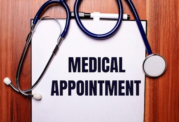 Auf einer holzoberfläche liegen ein stethoskop und ein blatt papier mit der aufschrift medical appointment. flach liegen. medizinisches konzept