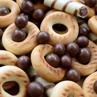 Auf einer holzoberfläche liegen knusprige süße röhrchen, schmelzende schokoladenbälle und gelbe bagels