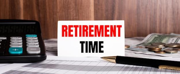 Auf einer holzoberfläche liegt ein stift mit taschenrechner und eine weiße karte mit den worten retirement time