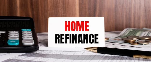 Auf einer holzoberfläche liegt stift mit taschenrechner und weißer karte mit worten home refinance