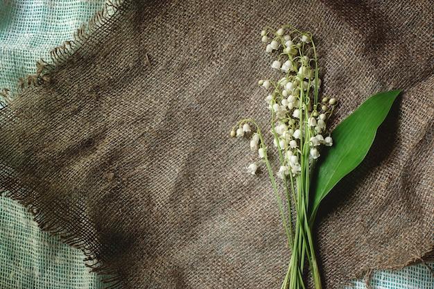 Auf einer matten serviette liegt ein strauß weißer maiglöckchen